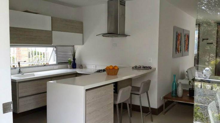 Cocina con mueble inferior y superior, barra y mesón en Quarztone, campana, horno y cubierta.