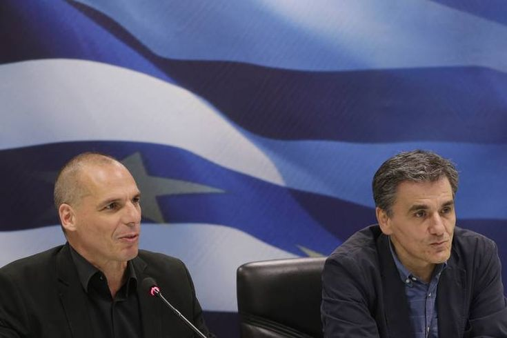 Outgoing Greek Finance Minister Yanis Varoufakis, left, speaks as the new Finance Minister Euclid Tsakalotos...