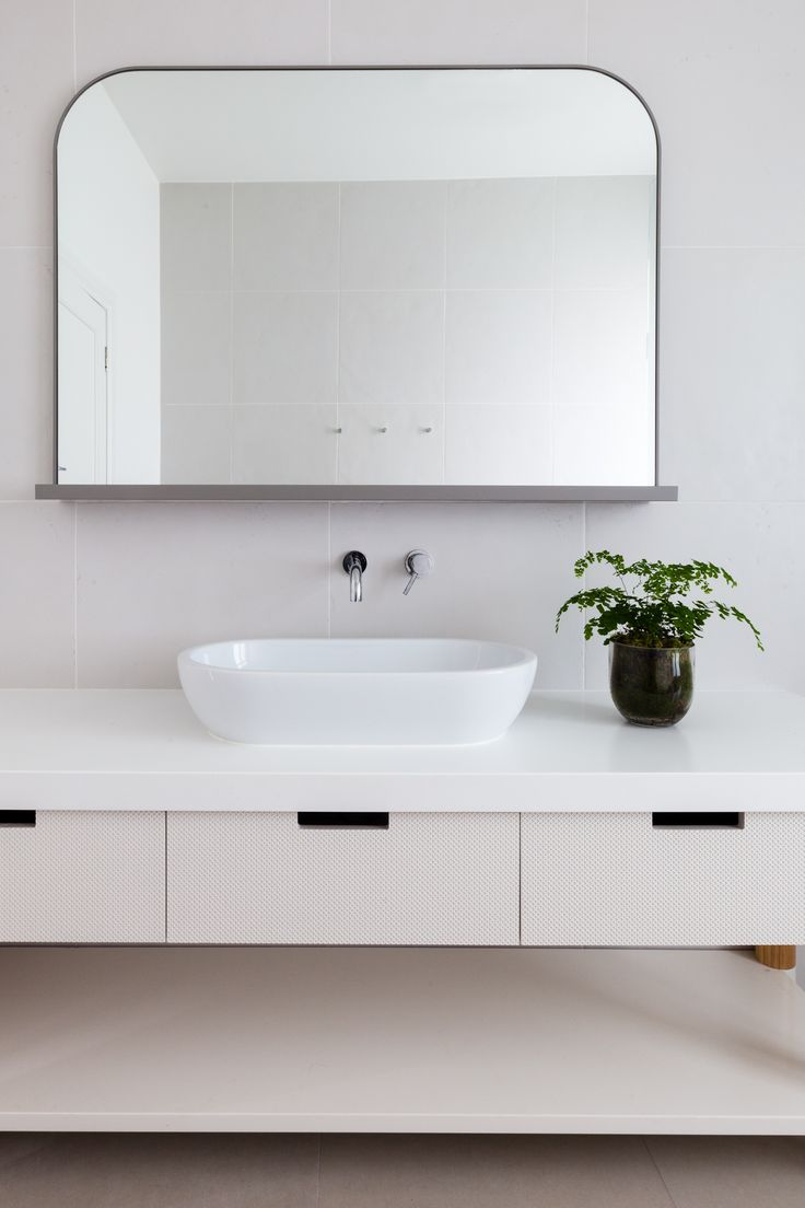 Mirror and sink shapes good for limited space, placed asymmetrically on grey marble. Wrought iron brackets somewhere.