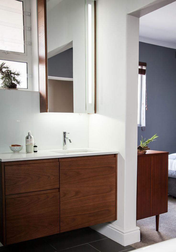 The oak veneer joinery works well with the white basin glass splash back.