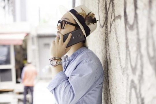 Designer Choi Bum Sik on his phone with his fedora hat on.