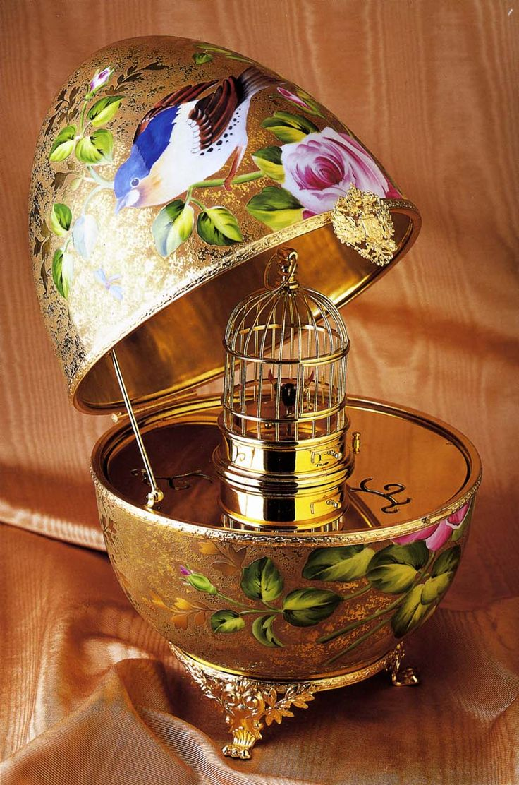 Limoges 24k Gold Birdcage Musical Egg with Singing Bird :: A limited edition piece, it is hand-painted, 24K gold incrustation Limoges porcelain egg. Like all Faberge Imperial eggs, each egg comes with a surprise. The surprise in this egg is a miniature Reuge (swiss-made) version of the famous singing bird in a gilded cage. The bird has real antique feathers and naturalistically moves its beak and wings as it sings.