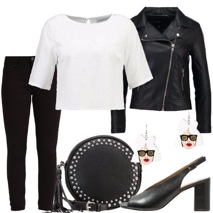 I jeans neri con vestibilità skinny sono abbinati alla camicetta bianca a piccoli pois neri con maniche tre quarti e chiusa con un bottone sul retro e ad una giacca di finta pelle nera chiusa da una lunga cerniera. I sandali sono neri con tacco largo alto circa sette centimetri e la borsa è rotonda, nera, in finta pelle e decorata con piccole borchie. Per finire, gli orecchini in metallo rappresentano un volto di donna e sono smaltati.