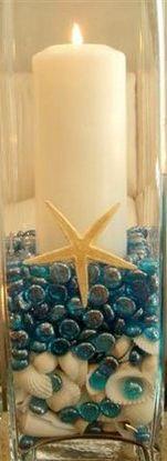 Schelpen vaas. Nodig: Hoge vaas, Witte schelpen, Blauwe glas nuggets, Zeesterren. Stompkaars. Werkwijze: Leg op de bodem een laag witte schelpen en hierop de glasnuggets. Schik de kaars in het midden van de vaas. En zet aan de zijkanten de zeesterren.
