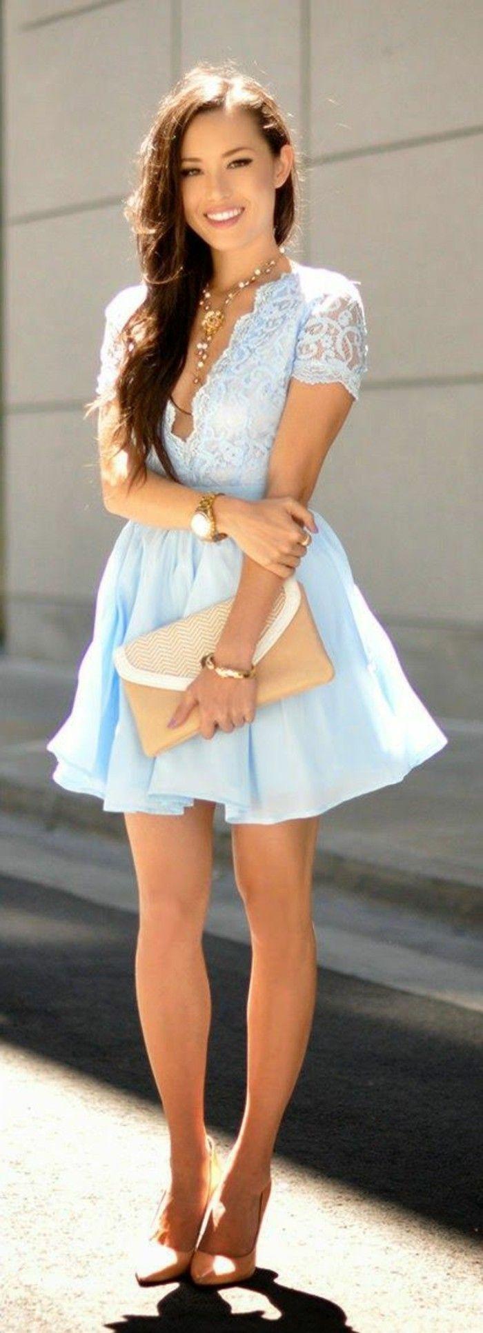 Jessica Ricks légèrement bronzée, souriante avec des cheveux de poitrine-longueur en une robe de soirée courte en dentelle bleu avec une décolleté profonde et manches courtes, escarpins nus, montre-bracelet d'or portante un embrayage taupe