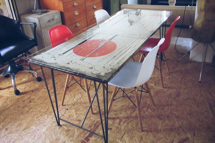 Industriële tafel gemaakt van een oude deur met een glazen blad op een onderstel van getorst staal.