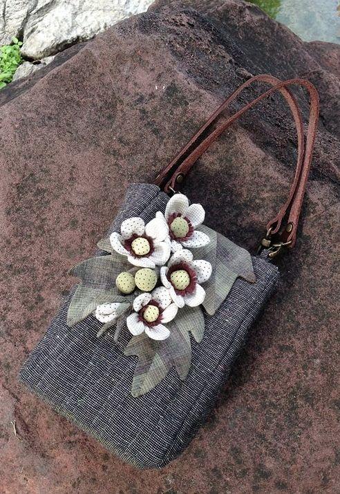 long, slim bag; floral embellishments, leather handles