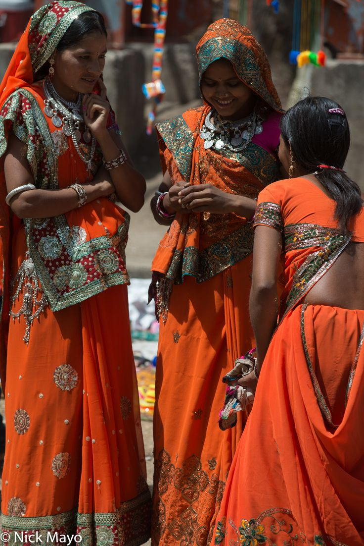 Bakhatgarh, Madhya Pradesh, India (2016) Three Bhil girls in orange wearing traditional head scarves and necklaces by Nick Mayo