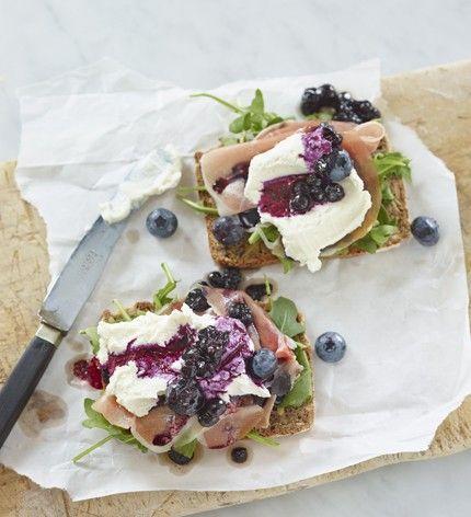 Rågbröd med chèvrekräm, serranoskinka, rucola och blåbärsvinägrett.
