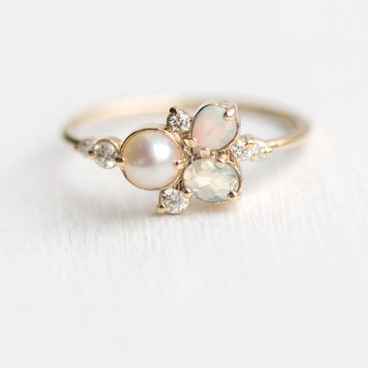 Our new cluster ring design features an Akoya pearl, oval opal, pear opal and tiny diamond accents, prong set in your choice of 14k gold yellow, white or rose!