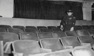 Fifteen police officers surround the movie theater, and four officers are needed to subdue Oswald inside. At 1.51pm police report him in custody. In this photo, a Dallas Police Officer points to the seat at the Texas Theatre where Lee Harvey Oswald was sitting when police entered to arrest him