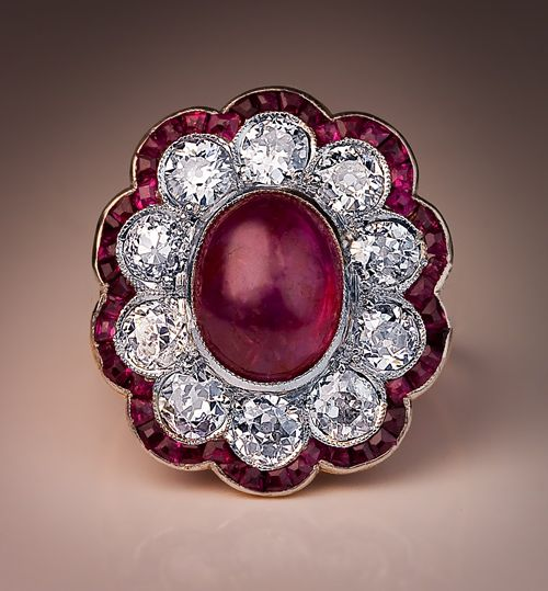 An Edwardian Era Antique Ruby and Diamond Engagement Ring, Circa 1910. This finely crafted fancy cluster ring features an oval cabochon cut ruby center in a milgrain platinum setting, framed by bright white and sparkling ten Old European cut round diamonds which, in turn, are outlined with a curvaceous border of tiny calibre-cut rubies.