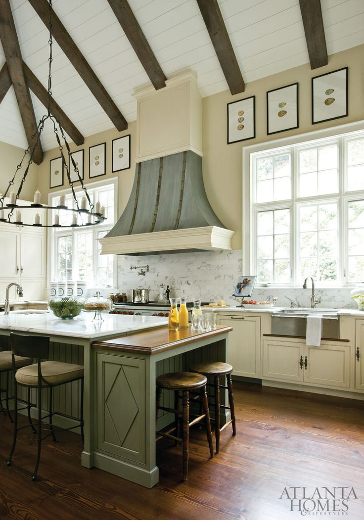 Ceiling beams and walls of windows provide plenty of eye candy in the kitchen; Designer Amy Morris simply added small touches such as the watercolor egg prints and a rugged torch-style chandelier to freshen the space.