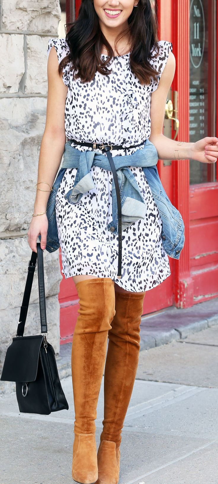 Polka dot spring dress paired with over the knee brown boots and a denim jacket tied around the waist