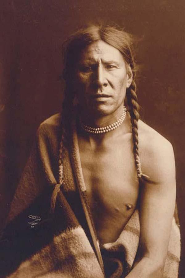 Above we show a moving photo of Heavy Shield. It was made in 1900 by Edward S. Curtis.    The illustration documents Half length portrait of a Native man.    We have compiled this collection of artwork mainly to serve as a vital educational resource. Contact curator@old-picture.com.
