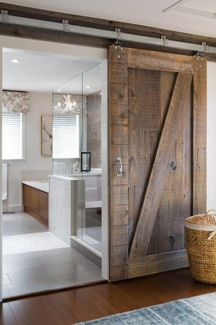 Rustic Master Bathroom with Wood enclosed tub, Hardwood floors, Chandelier, White faux antler chandelier, Sliding barn door