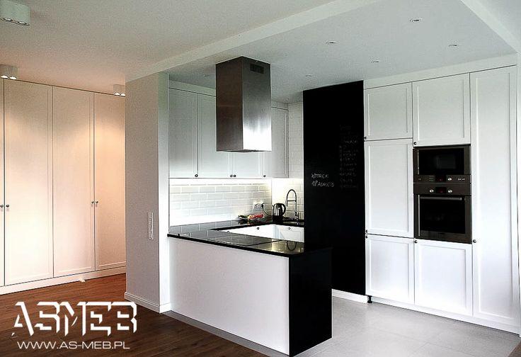 Przestronny aneks kuchenny, połączony z salonem, doświetlony dużym oknem. W tle szafa przedpokojowa z zastosowaniem frontów ramkowych nawiązujących stylem do kuchni.