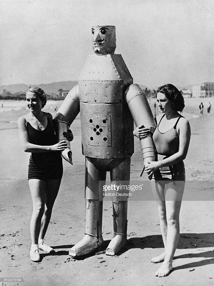 Beachgoers standing with Mac the Mechanical Man. The radio controlled robot weighs 250 pounds and is seven and a half feet tall and is operated by inventor and builder Leighton Hilbert.