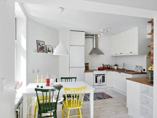 biała kuchnia z drewnianym blatem i białym stołem z zielonymi i żółtymi krzesłami - Lovingit.pl