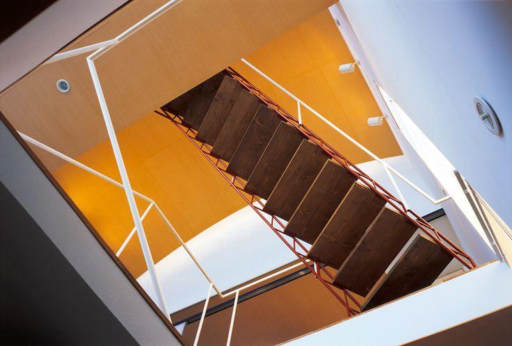 吹き抜けに斜めにかかる階段を下から見上げる