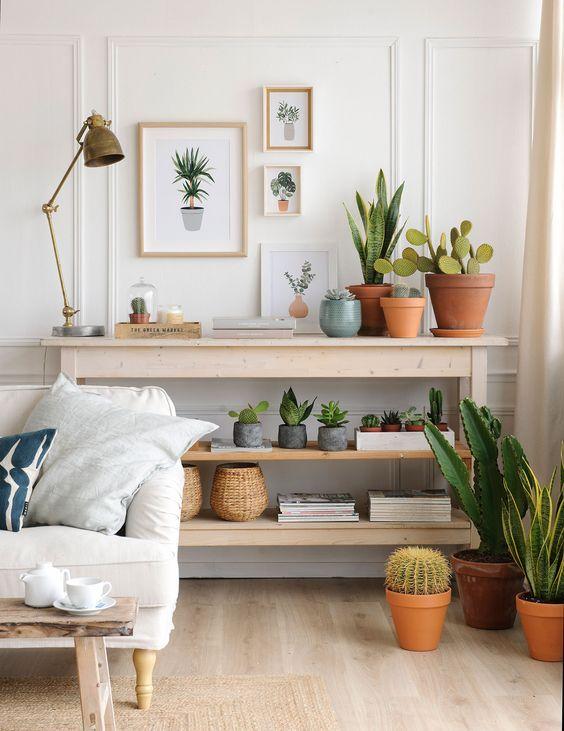 Rincón de salón con mueble en estantes, plantas y composición de cuadros con motivos vegetales