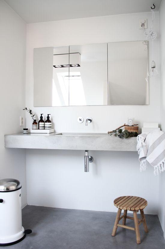 concrete vanity + white walls + exposed bulb + minimal bathroom