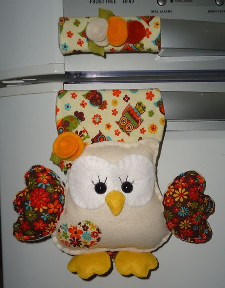 Confeccionado em feltro e tecido tricoline 100% algodão, com enchimento de fibra siliconizada antialérgica. Produto 100% artesanal, peça exclusiva, lavável. A corujinha possui aproximadamente 15 cm. Acabamento com apliques, flores e folhas de feltro e fios de rami. O fechamento é feito com velcro, o que possibilita um ajuste perfeito ao seu refrigerador. Obs.Se quiser, ao fazer sua encomenda especifique as cores predominantes desejadas para o tecido e as flores. R$ 38,50