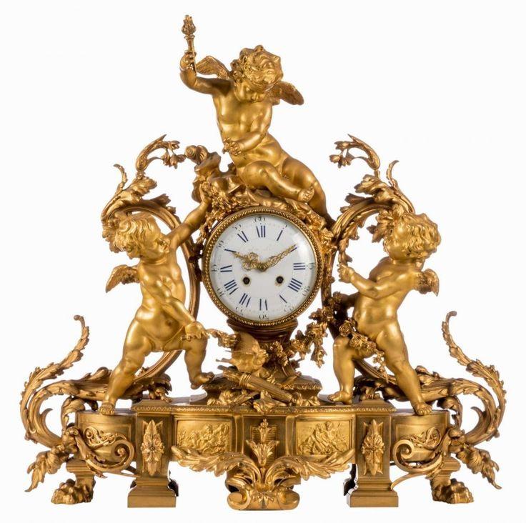 A late 19thC gilt bronze neoclassical mantel clock, the movement carried by three cupids, the dial m — Uhren: Standuhr, Wanduhr, Tischuhr, Armbanduhr, Taschenuhr, Rolex, GMT Master, Submariner, Cartier, Tank, Jaeger-LeCoultre, Patek Philippe, Breguet, Glashütte, IWC