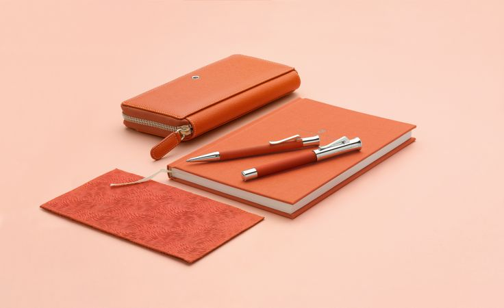 The ensemble includes the Guilloche Fountain Pen and Guilloche Twist Ballpoint Pen. The writing instruments' name comes from the grain guilloche, an intricate engraving that allows the surface relief to shimmer depending on how the light hits it. #grafvonfabercastell #orange #fountainpen