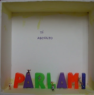 "This display case is consecrated to the opening, to the dialogue. The inscription ""ti ascolto""/""I am listening to you"" resides in an empty and neutral space in the background: it means that there is no prejudice, no preconception, only  the willingness to listen to whatever can be told, giving free hand, filling this open space with words, with a tale, with any form of communication."
