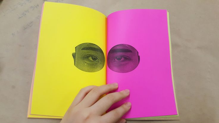 """Victoria KonI, Volume 1 (book detail). 2016. 50 photographs, hand bound, film photography on laser print. 5.5"""" x 8"""" // To remove possible anthropological or racial connotations, each set of eyes was printed on nonsensical coloured pages, the bright hues of which also play against the banality of the white-space style of design. The concept was inspired by the artist's fear of human interaction and eye contact. produced in conjunction with Publication Studios Vancouver"""