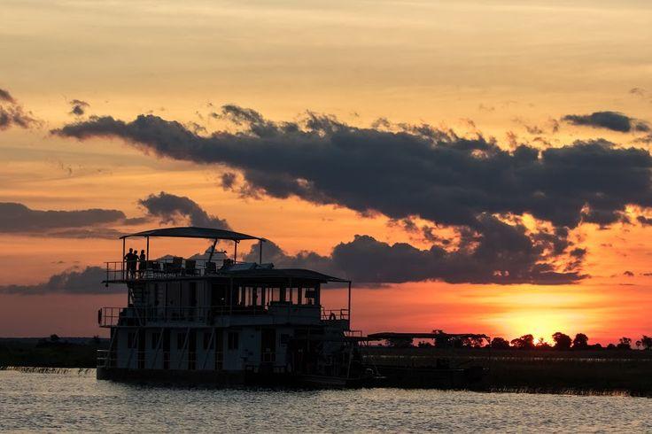 The Pangolin Voyager cruising along the Chobe river as the sun sets.