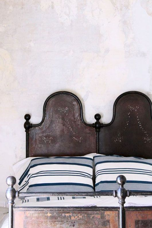 beautiful bed, blue striped pillows, double headboard, punched tin