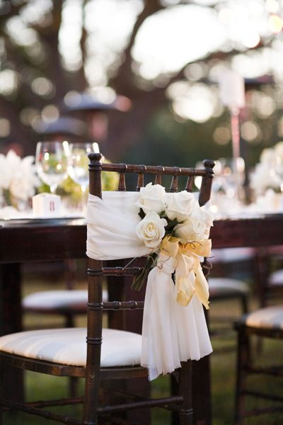 Wedding Chair Swag Decorations - A simple fabric tieback with flower arrangement contrasts well with the dark colour of this chair.