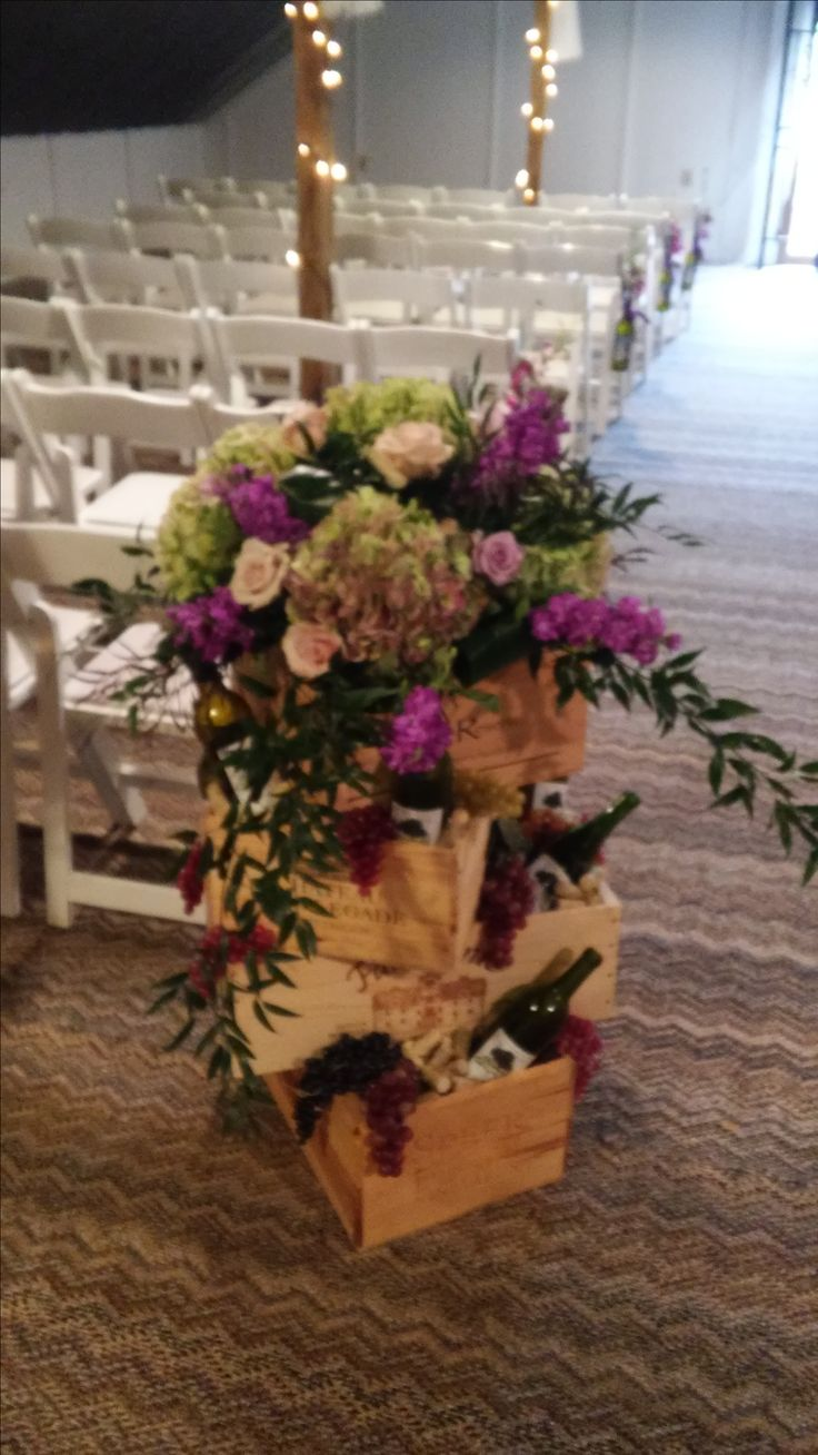 Wine themed wedding ceremony or reception arrangement  with antique hydrangea, lavender stock, cream roses and Italian ruscus arranged in wine crates with wine bottles.