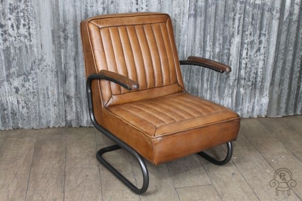 This tan leather armchair is based on a 1950s classic American car seat. It has a worn aged appearance to the leather. Matching sofa also in stock now...