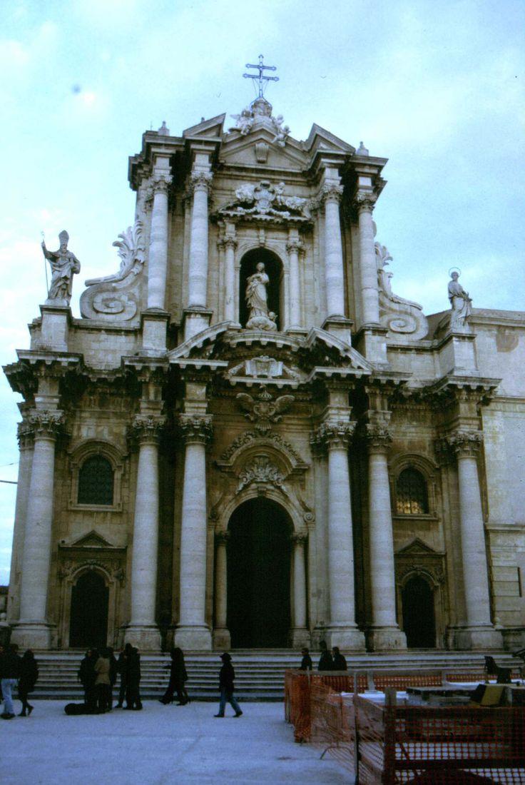 Dom van Syracuse. De kerk kent meerdere bouwperioden. Het is gebouwd rond de restanten van een oude Griekse tempel. De barokke gevel ontstond van de hand van Andrea Palma (1728-1754). Syracuse (Sicilië). De kerk is gewijd aan de heilige maagd Maria. Volgens mij is zij ook als beeldhouwwerk te zien bovenin het midden van de voorkant van de kerk. Links van haar staat de paus en rechts een heilige met een krans om het hoofd. De kerk is zeer overvloedig versierd met ornamenten en zuilen.
