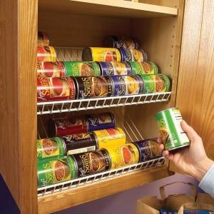 Use wire closet racks tilted for can storage in your cabinets.  Great idea that will save much space!