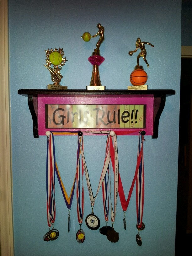 Medal display. Trophy shelf - bought one of these shelves at Hobby Lobby and painted it to match the bedroom colors for all of K's medals and softball trophies.
