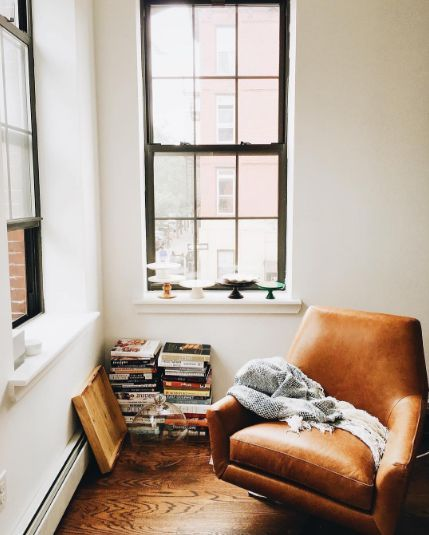 tan arm chair, open windows, books @thecoveteur