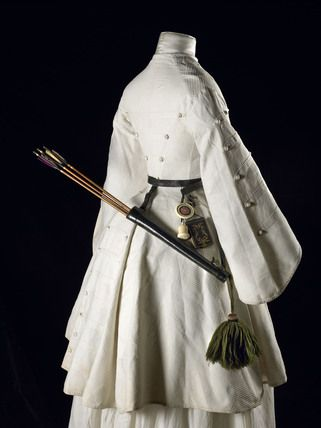 A side view of a three quarter length white cotton Marcella archery jacket with pagoda sleeves, trimmed in military style with braid and covered conical buttons. Worn by Mrs. Fanny Giveen (1833-1863), the wife of Captain Xavier Giveen.