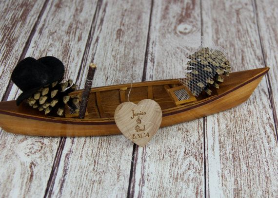 Fishing canoe cake topper is adorable for an outdoorsy couple. Pinecones have been turned into a Mr. & Mrs. pinecone including the top hat and