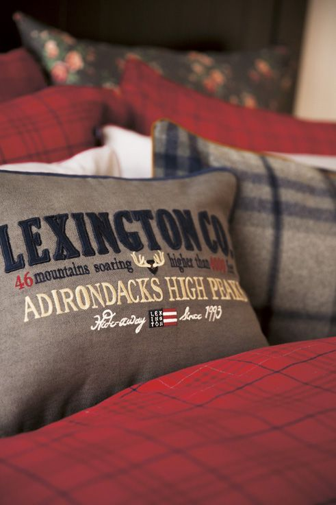 The Lexington Adirondack Sham, a Holiday cotton twill sham in grey with patched and embroidery details at the front. Blue piping and with a zip closure at the back.