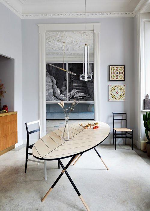 Dalla cucina-pranzo si intravede il soggiorno, dietro lo stipite in legno realizzato su disegno di Pietro Russo. Suo anche il tavolo Piuma...