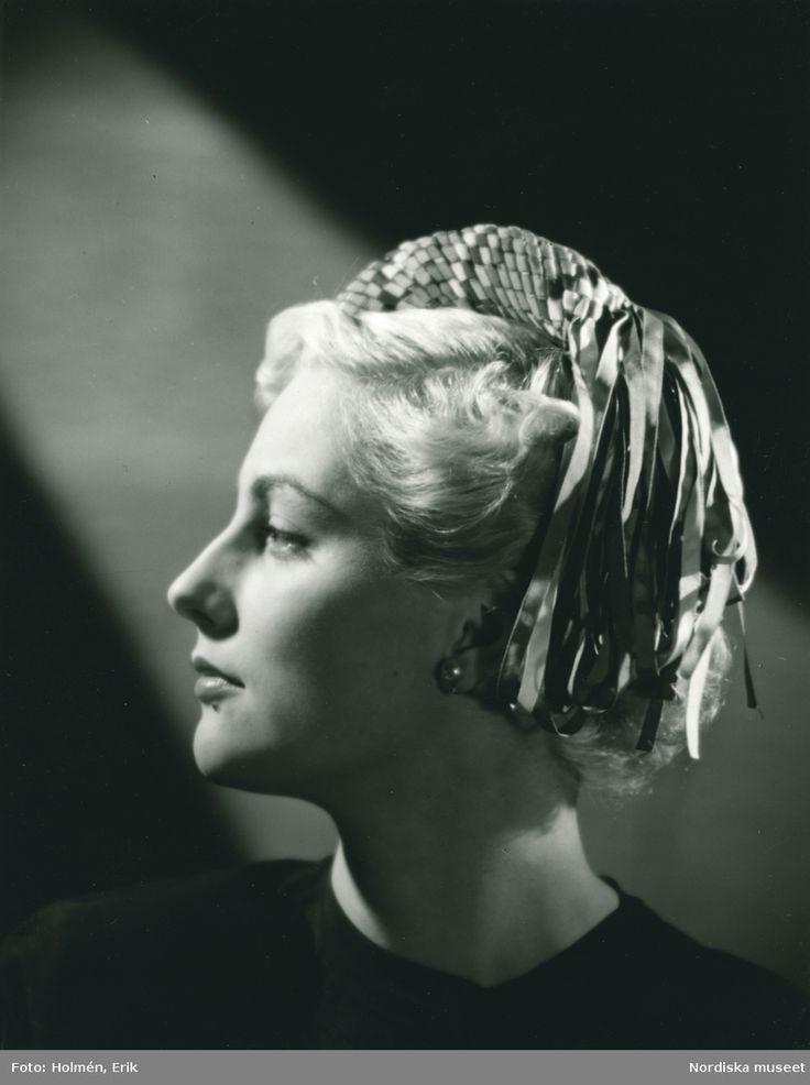 1949. Modell efter Simone Cange. Porträtt av kvinna med hatt i smultronfärgad filt med brätte av flätade sidenband i en mängd färger. Garneringen bildas genom att banden avslutas i nedhängande öglor. Foto: Erik Holmén