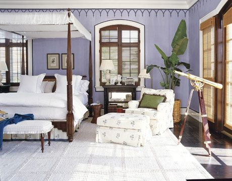 In a plantation-like master bedroom in a Florida house with a stenciled frieze, antique pier tables are the perfect bedside height for the unusually high British Colonial-style bed; the fabric of the canopy's valance is from William Ashby, and the bedskirt, in Hinson's Dottery Blue on off-white, matches the custom club chair and ottoman. The pattern of the Stark carpet is echoed on the master bathroom floor. Custom wall color is glazed and combed. Designer Robin Bell designed the decorative…