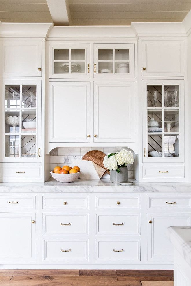 The Kitchen Buffet Cabinet Features White Marble Countertop Brass Hardware Stacked Cabinets With Glass