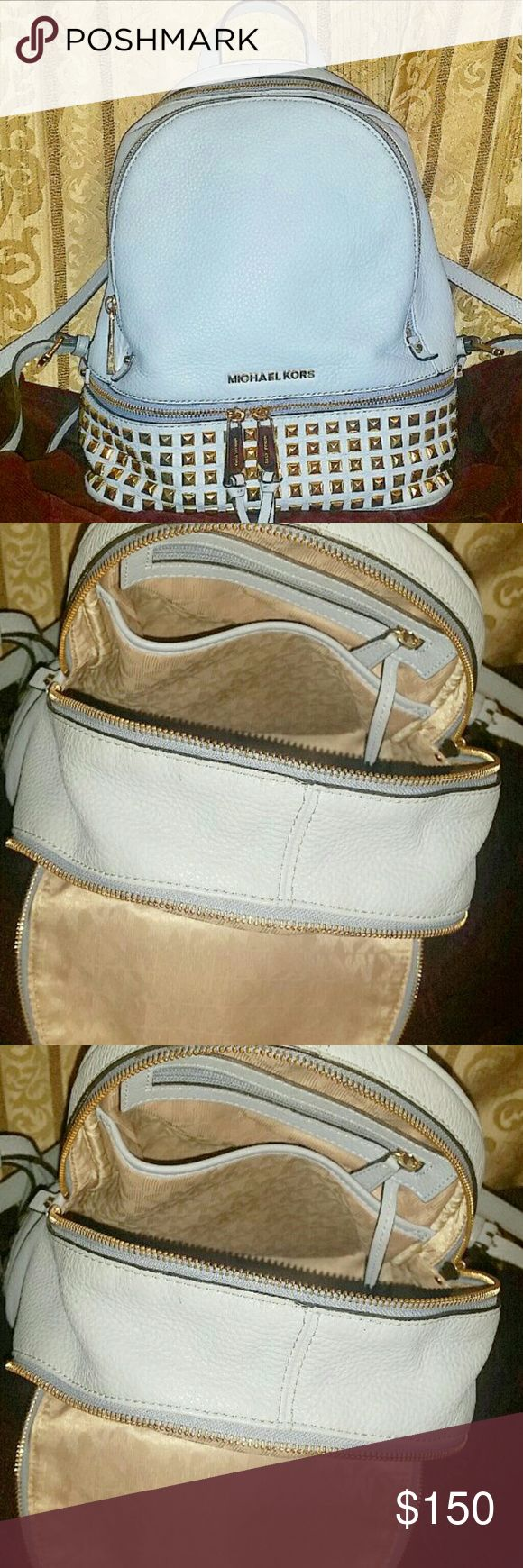 Michael Kors studded backpack purse Lovely Baby blue leather bookbag Michael Kors backpack  Gently USED  AUTHENTIC MICHAEL KORS Studded  leather BAG  ***Looks great from the outside but does have a small stain in one of the small slip pockets inside. Spilled some blush/lipstick***as shown in the 3rd picture ****  Smoke free home  Gold Michael Kors hardware  Small/Medium size.   Placed waterbottle in the last picture for size reference  Not big enough for textbooks, but big enough for a…