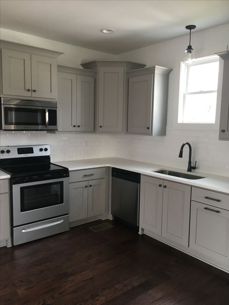 Gray kitchen cabinets, white quarts countertops, subway