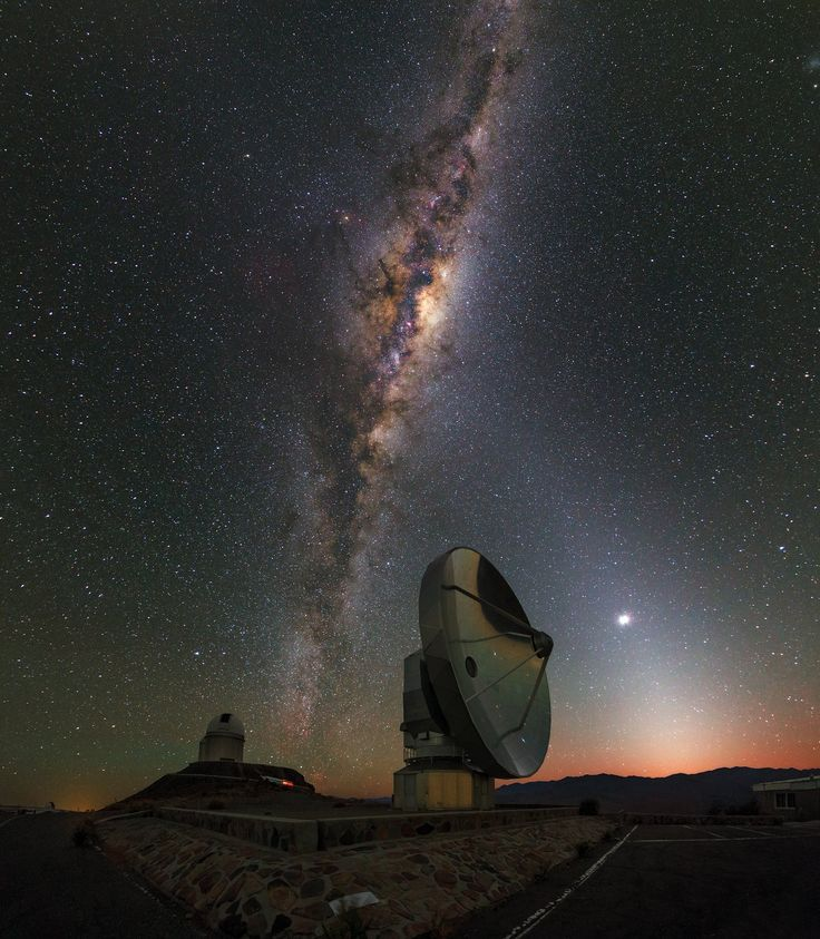 La Silla Dawn Kisses the Milky Way | This picture was taken just before dawn at the La Silla Observatory, in outskirts of the Chilean Atacama Desert. A layer of orange hovering over the horizon announces the imminent arrival of the Sun. These first hints of daylight are kissed by the Milky Way, which stretches out across the entire night sky. This view of our home galaxy is covered with dark patches, formed from dust particles blocking the light behind them.